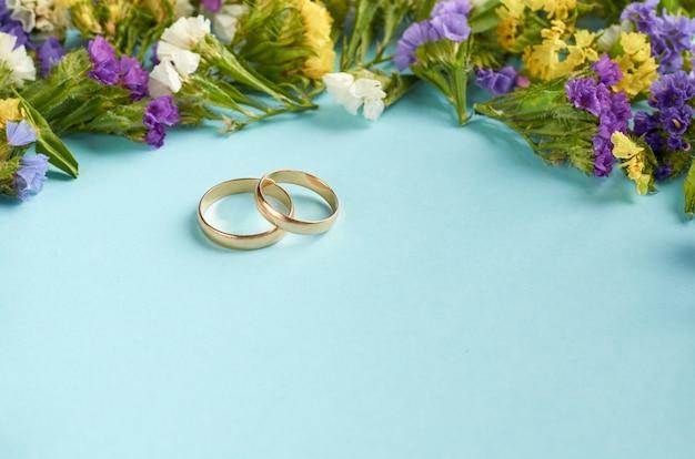 Anéis de ouro com flores coloridas na superfície azul, modelo casamento.