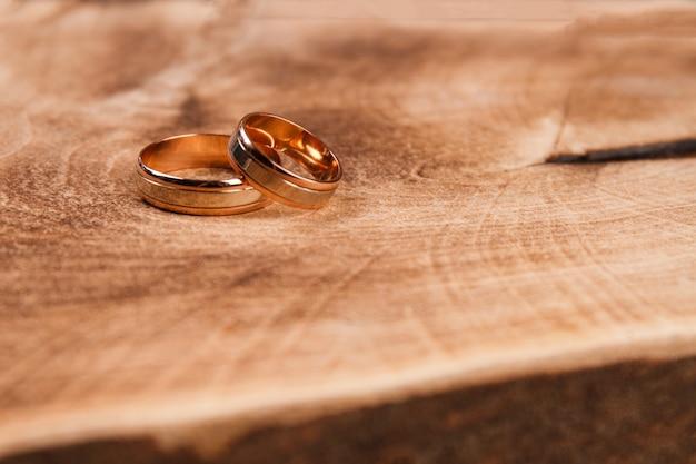 Anéis de ouro de close-up na madeira.