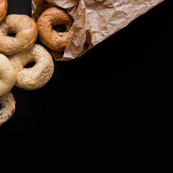 Anéis de pão acabado de cozer contra o fundo preto