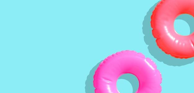 Anéis de piscina inflável sobre fundo azul.