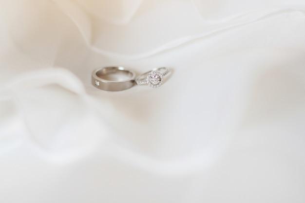 Anéis de prata e diamante de noivo e noiva em um pano branco no dia do casamento.