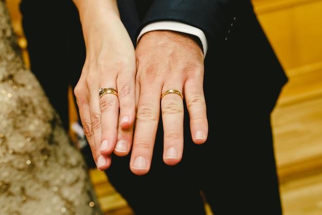 Anéis de recém-casados mostrados nas mãos da noiva e do noivo.