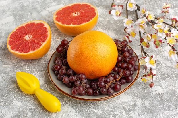 Anéis de toranja fresca de vista frontal com uvas na superfície branca