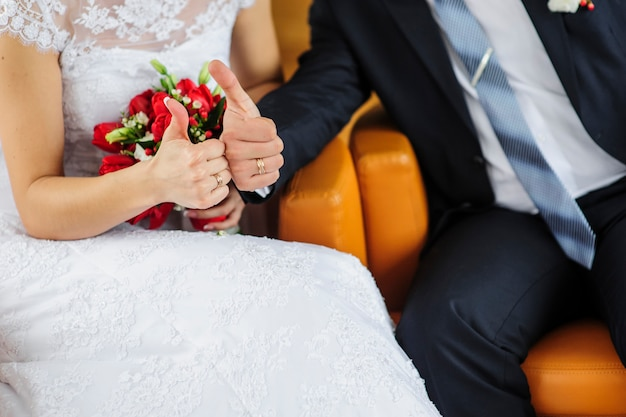 Anéis na mão, vestidos como uma noiva e noivo