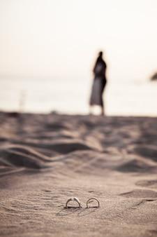 Anéis na praia com a noiva e o noivo em fundo