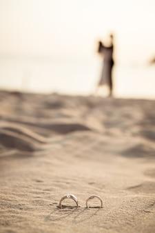 Anéis na praia com silhuetas dos noivos