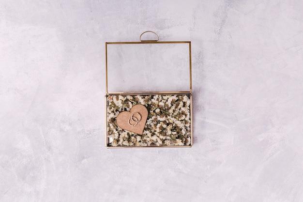 Anéis no coração de ornamento entre flores na caixa