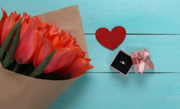 Anel com um diamante em uma caixa de presente, coração e um buquê de tulipas vermelhas sobre fundo azul de madeira. aniversário, dia dos namorados ou proposta de casamento. vista do topo