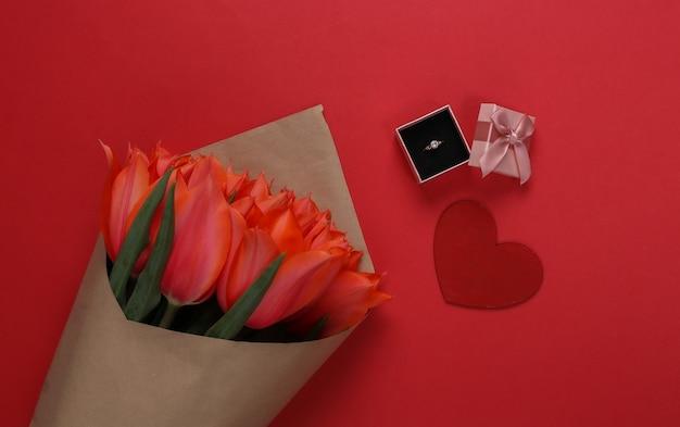 Anel com um diamante em uma caixa de presente, coração e um buquê de tulipas vermelhas sobre fundo vermelho. aniversário, dia dos namorados ou proposta de casamento. vista do topo