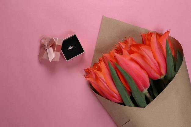 Anel com um diamante em uma caixa de presente e um buquê de tulipas vermelhas em um fundo rosa. aniversário, dia dos namorados ou proposta de casamento. vista do topo