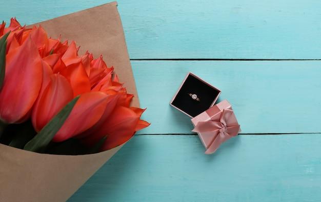 Anel com um diamante em uma caixa de presente e um buquê de tulipas vermelhas sobre fundo azul de madeira. aniversário, dia dos namorados ou proposta de casamento. vista do topo
