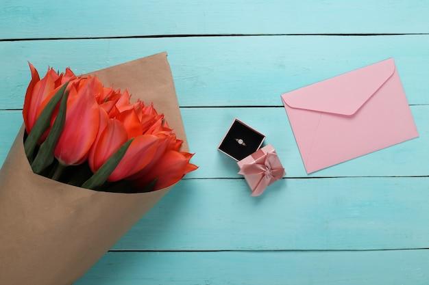 Anel com um diamante em uma caixa de presente, envelope e buquê de tulipas vermelhas sobre fundo azul de madeira. aniversário, dia dos namorados ou proposta de casamento. vista do topo