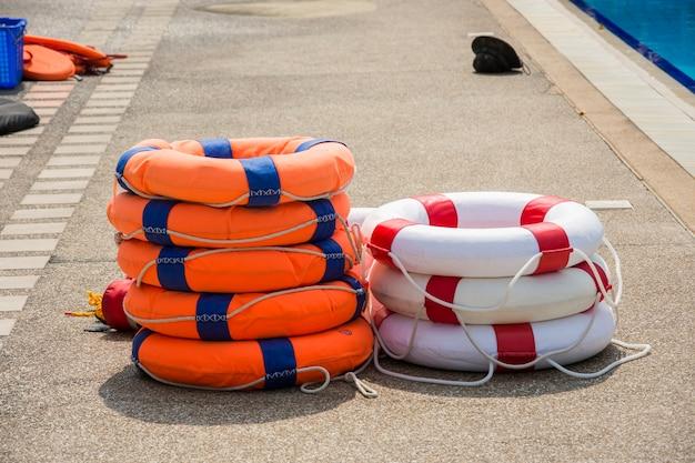 Anel de bóia laranja e branco estar do lado da piscina