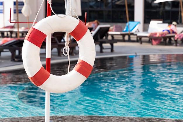 Anel de bóia salva-vidas vermelho perto da piscina