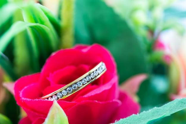 Anel de casamento descansando em uma flor rosa falsa