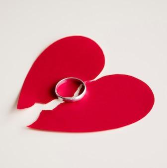Anel de casamento e coração de papel quebrado