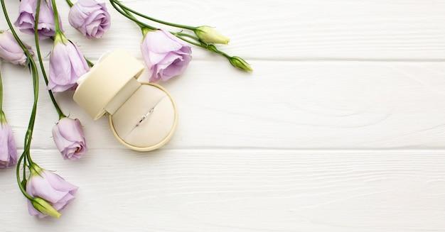 Anel de casamento e flores copiam espaço