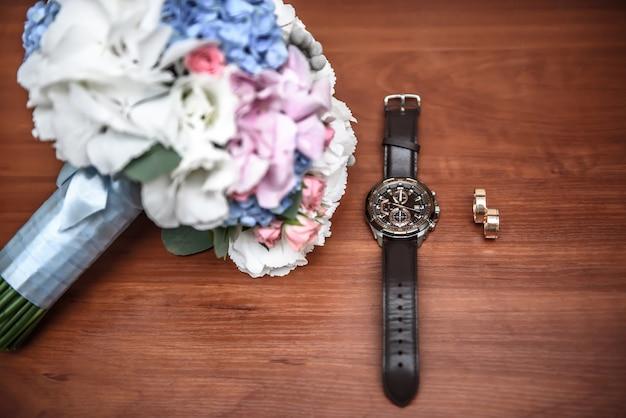 Anel de casamento e relógio do noivo na mesa com o buquê de casamento