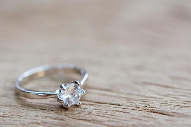 Anel de diamante, aliança de casamento na prancha de madeira com espaço de cópia
