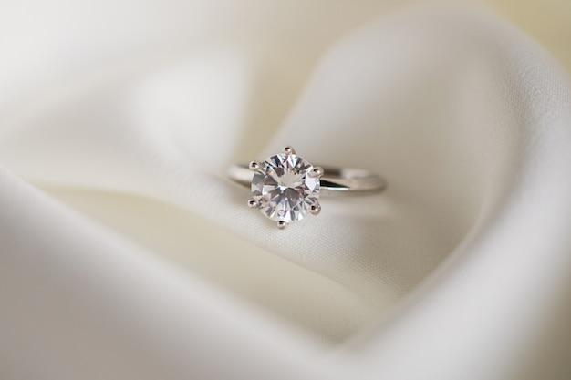 Anel de diamante close-up em tecido branco