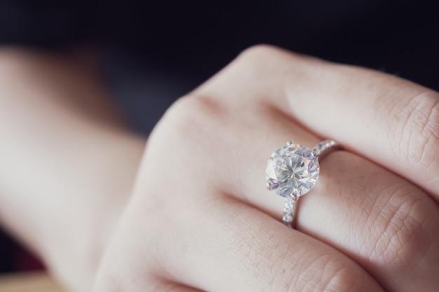 Anel de diamante de noivado no dedo da mulher, close-up