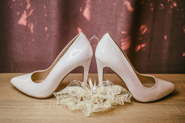 Anel de diamante de ouro entre par de sapatos de salto alto brancos
