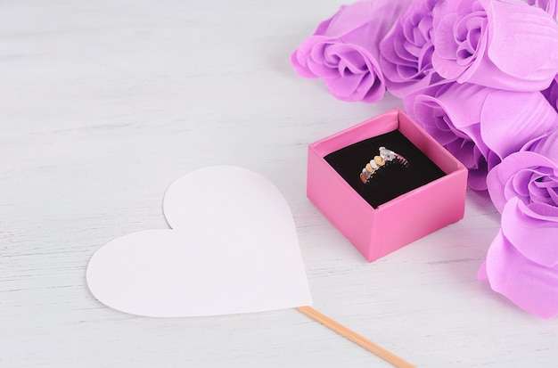 Anel de diamante dourado em caixa rosa com buquê de rosas