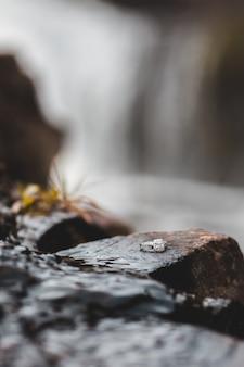 Anel de diamante em pedras molhadas