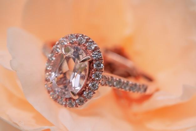 Anel de diamante rosa em fundo de flor rosa