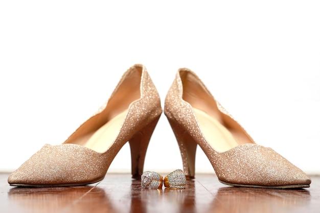 Anel de diamantes e sapatos dourados para casamento em madeira.