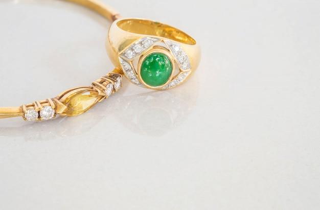 Anel de jade verde closeup e pulseiras de ouro no chão de pedra de mármore cinza turva