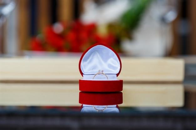 Anel de joias preciosas de ouro de noivado para uma menina em uma caixa vermelha em um fundo de frutas
