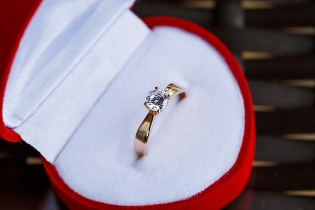 Anel de joias preciosas de ouro de noivado para uma menina em uma caixa vermelha