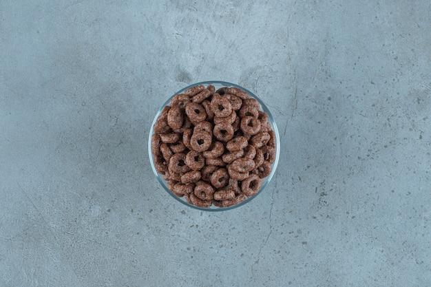 Anel de milho de chocolate em um pedestal de vidro, no fundo azul.