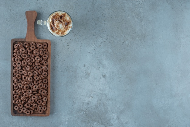 Anel de milho em uma placa ao lado do copo de café com leite, sobre o fundo azul.
