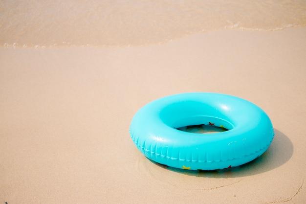 Anel de natação inflável azul na praia de areia