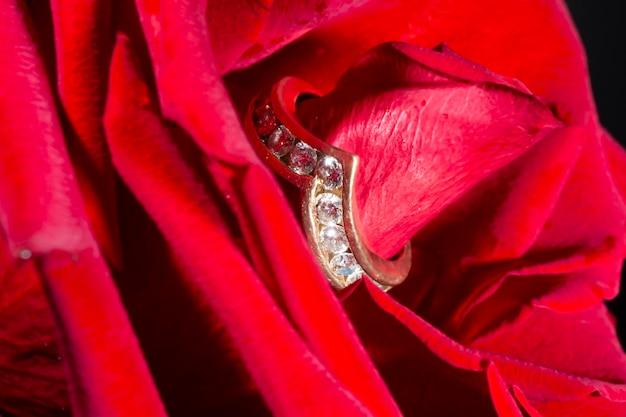 Anel de noivado de diamante com um caminho de diamantes e uma rosa vermelha. o conceito é uma oferta para se tornar minha esposa