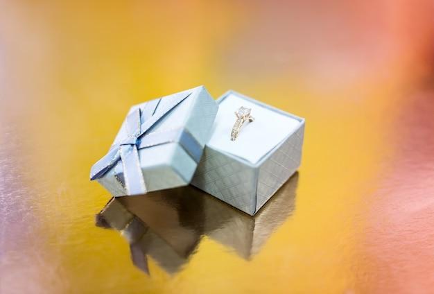 Anel de noivado dourado em caixa de presente prata