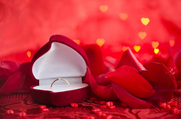 Anel de noivado e pétalas de rosa vermelhas