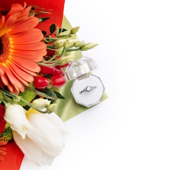 Anel de noivado em uma caixa de presente com buquê brilhante de flores. a oferta para se casar. presente para o dia dos namorados. proposta de casamento para mulher amada. símbolo de amor e casamento.