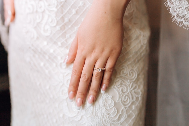 Anel de noivado na mão da noiva com pedras preciosas e bela manicure francesa