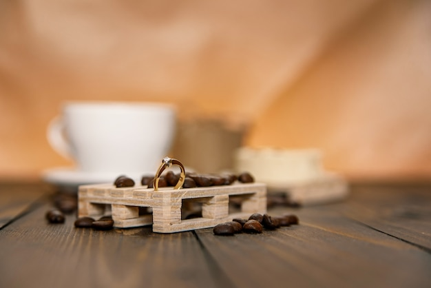 Anel de noivado no suporte de madeira com grãos de café e xícara de café com bolo de diamante
