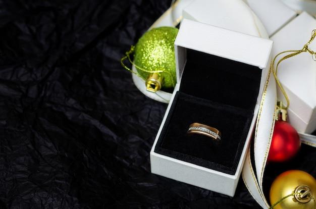 Anel de ouro com diamantes em caixa de presente branca.