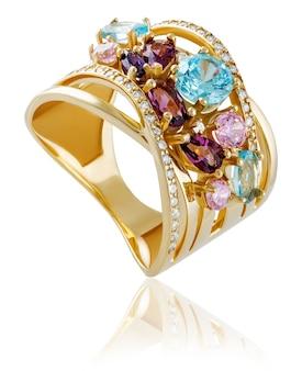 Anel de ouro com pedras preciosas em um fundo branco com reflexo