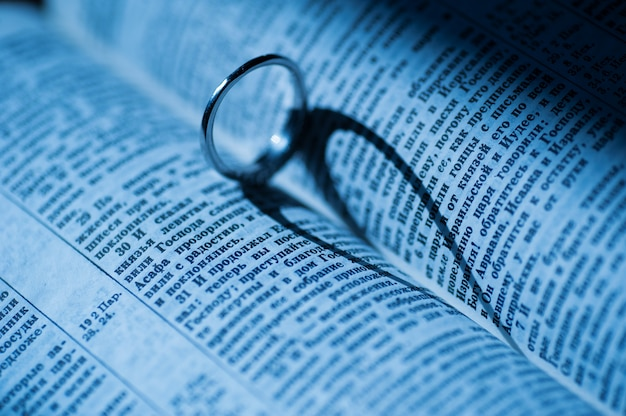 Anel de ouro faz sombra em forma de coração no livro