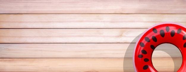 Anel de piscina inflável de melancia em fundo de madeira.