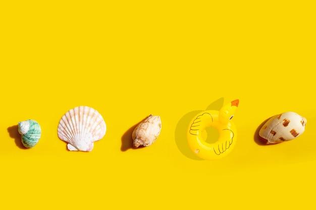 Anel de piscina inflável de pato com conchas exóticas em fundo amarelo.