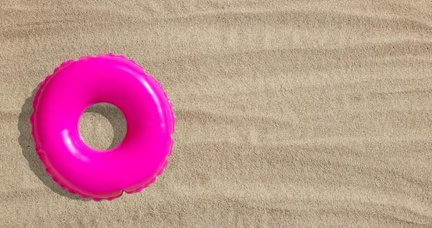 Anel de piscina inflável rosa na areia