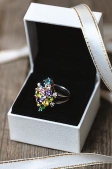 Anel de prata com gemas coloridas em caixa de presente branca