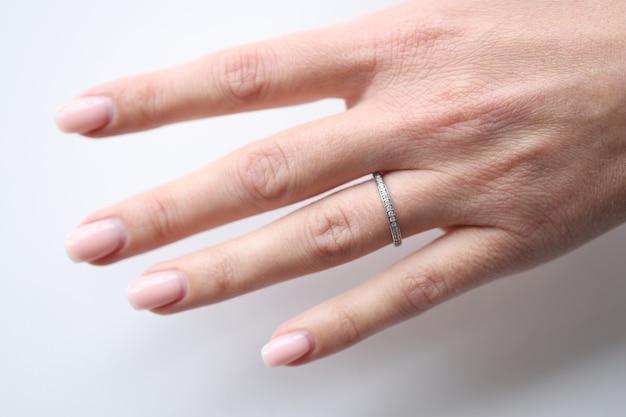 Anel de prata com pequenas pedras na mão da mulher